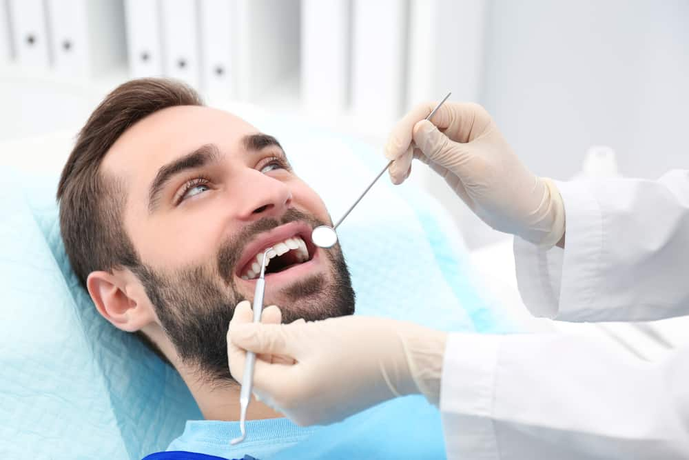 Dentist examining young man's teeth with mirror and probe in hospital